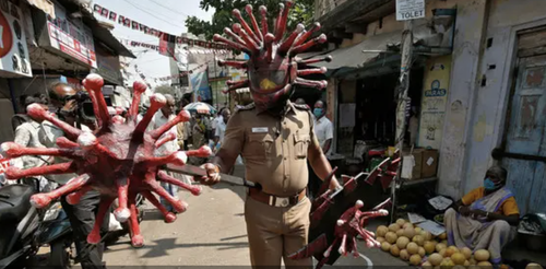 A police officer wearing a helmet and holding a shield molded to resemble the coronavirus patrols a market in Chennai.